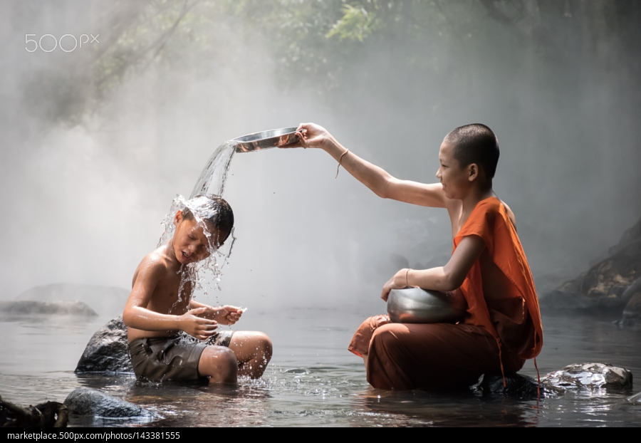 Monk and boy are playing whit water at stream.